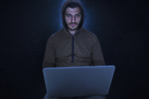 Young computer hacker wearing hooded shirt using laptop against black background - FSIF01285