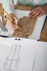 High angle view of female designer drawing sketch on paper at studio - FSIF01346