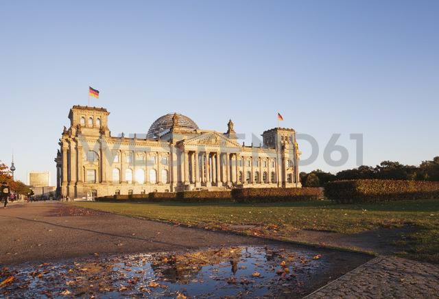 Germany, Berlin, Regierungsviertel, Reichstag building with German Flags in autumn, TV tower in background - GWF05431