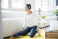Woman at home wearing headphones hoovering the floor - MOEF00800