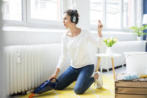Woman at home wearing headphones hoovering the floor - MOEF00800