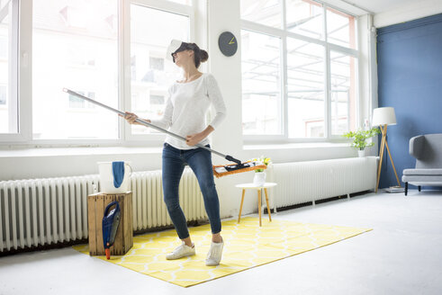 Vital woman at home wearing VR glasses wiping the floor - MOEF00803