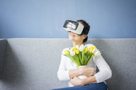 Smiling woman sitting on couch wearing VR glasses holding bunch of tulips - MOEF00806