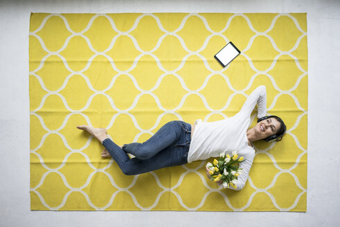 Smiling woman wearing headphones lying on carpet with bunch of tulips - MOEF00809