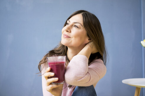 Smiling woman holding glass of juice - MOEF00815