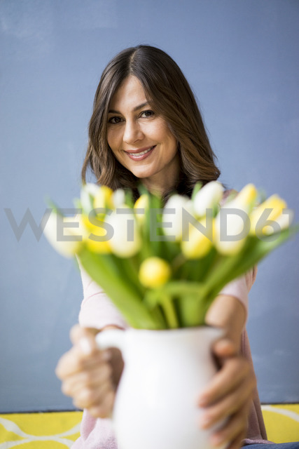 Portrait of smiling woman holding bunch of tulips in a jar - MOEF00818