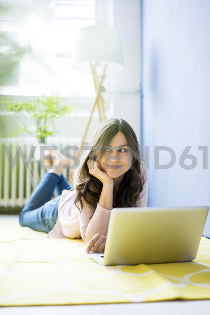 Smiling woman lying on floor with laptop - MOEF00824