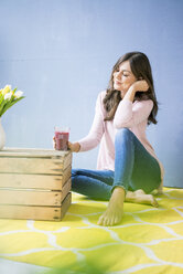 Smiling woman sitting on floor holding glass of juice - MOEF00827