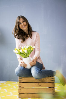 Portrait of smiling woman holding bunch of tulips in a jar - MOEF00830