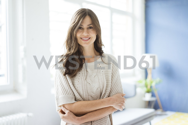 Portrait of smiling woman standing in bright room with window - MOEF00836