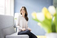 Portrait of smiling woman sitting on couch holding tablet - MOEF00842