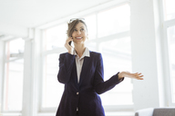 Smiling businesswoman on cell phone in bright room - MOEF00845