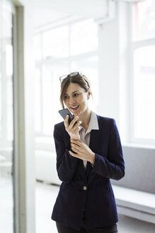 Businesswoman using cell phone in bright room - MOEF00848