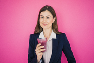 Portrait of smiling businesswoman in front of pink wall holding glass of juice - MOEF00851