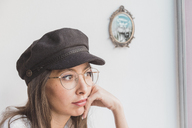 Stylish young woman wearing glasses and cap thinking - AFVF00005