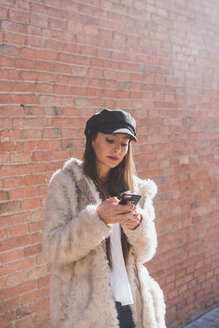 Stylish young woman in front of brick wall using cell phone - AFVF00008