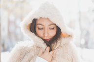 Portrait of young woman wearing hooded fur jacket - AFVF00017