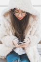 Stylish young woman sitting on a bench using cell phone - AFVF00020
