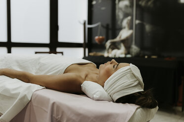 Young woman lying on lounge in a spa - OCAF00134