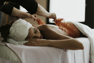 Young woman receiving a massage with feathers in a spa - OCAF00146