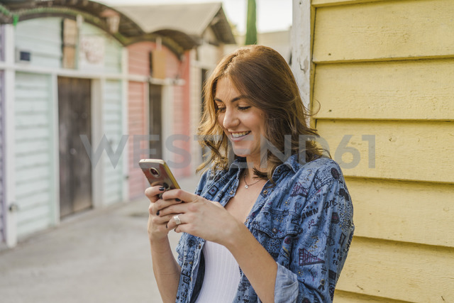 Portrait of smiling young woman using cell phone - AFVF00027