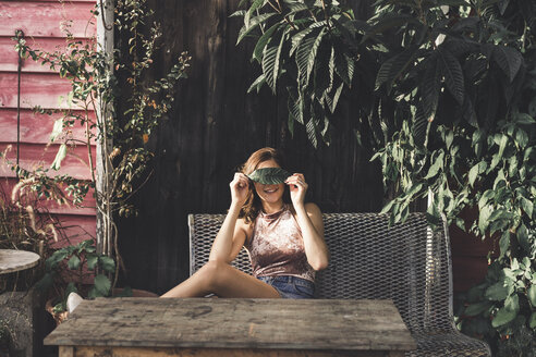 Young woman sitting on a bench outdoors covering eyes with a leaf - AFVF00033