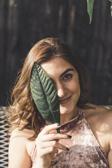 Portrait of smiling young woman  covering eye with a leaf - AFVF00036