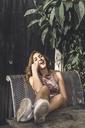 Portrait of laughing young woman sitting on bench outdoors - AFVF00039