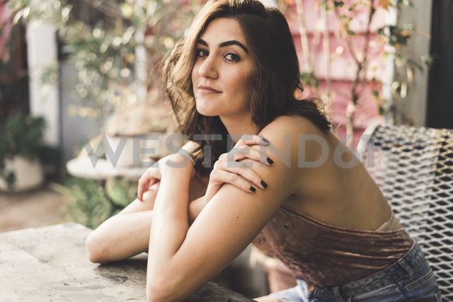 Portrait of young woman sitting on bench outdoors - AFVF00042