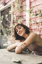 Portrait of happy young woman leaning on table outdoors - AFVF00045