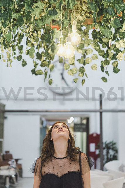 Smiling young woman looking up to shining lightbulbs - AFVF00054