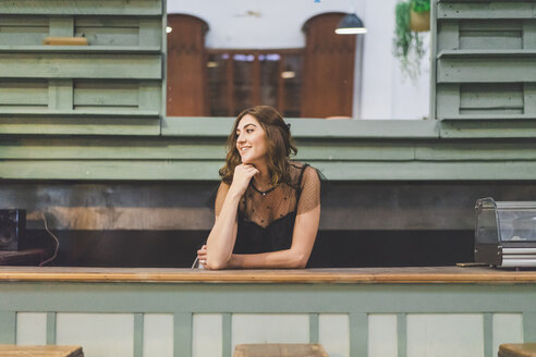 Smiling young woman leaning on old counter - AFVF00057