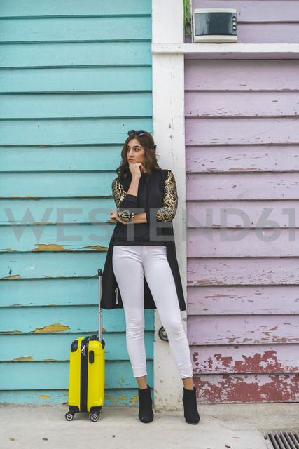 Young woman with yellow trolley bag waiting in front of wooden facade - AFVF00060