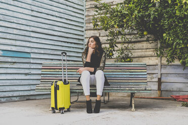 Young woman with yellow trolley bag waiting on a bench - AFVF00063