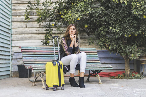 Young woman with a yellow trolley bag waiting on a bench - AFVF00066