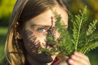 Portrait of girl with fern leaf at sunlight - SARF03582