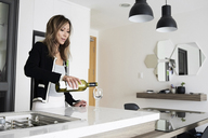 Woman serving wine in a glass at home - IGGF00401