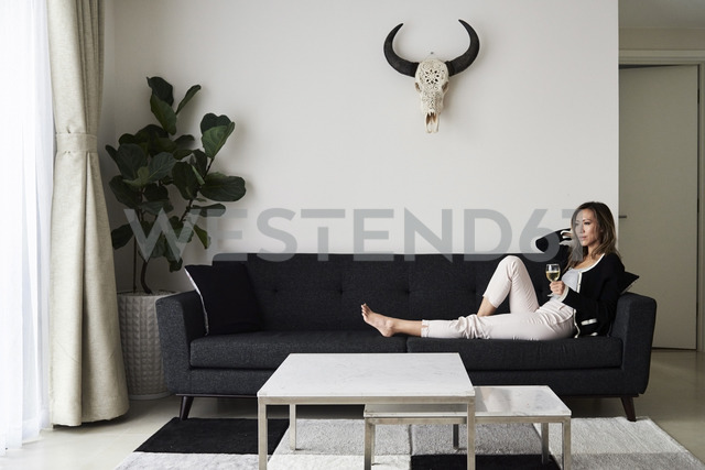 Woman having a glass of wine at home relaxing on sofa - IGGF00404