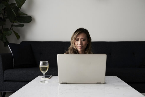 Woman at home with laptop and glass of wine - IGGF00407