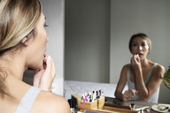 Woman at home using makeup applying lipstick in front of a mirror - IGGF00410