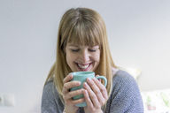 Portrait of laughing young woman with coffee mug - AFVF00067