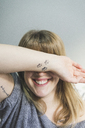 Laughing tattooed woman covering eyes with her arm - AFVF00076