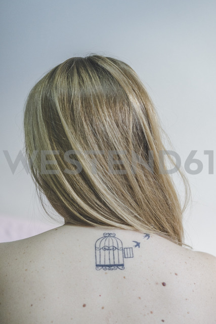 Back view of blond woman with tattoo on her neck - AFVF00079