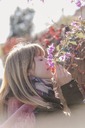 Woman smelling flowers outdoors - AFVF00082