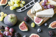 Plate with cheese, figs, grapes, blueberries, brambles, pecan, chopping board, knife - SARF03585