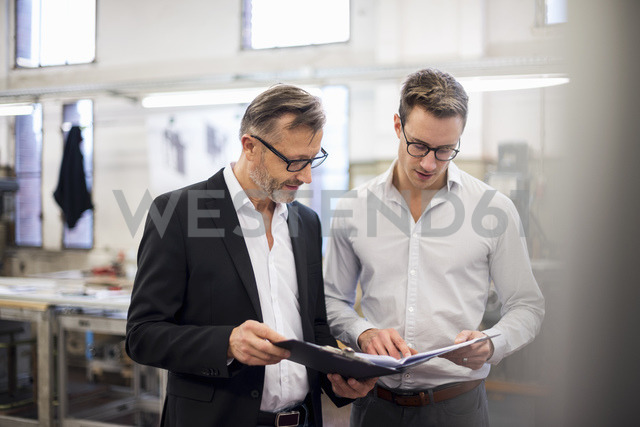 Two businessmen in factory looking at folder - DIGF03330