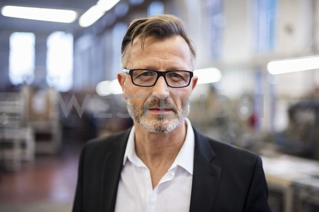 Portrait of confident mature businessman in factory - DIGF03333