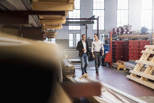 Two businessmen walking in factory storeroom - DIGF03339