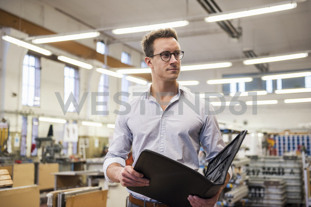 Young businessman in factory holding folder - DIGF03342