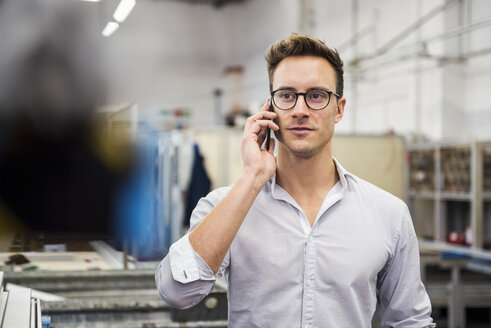Young businessman on cell phone in factory - DIGF03345